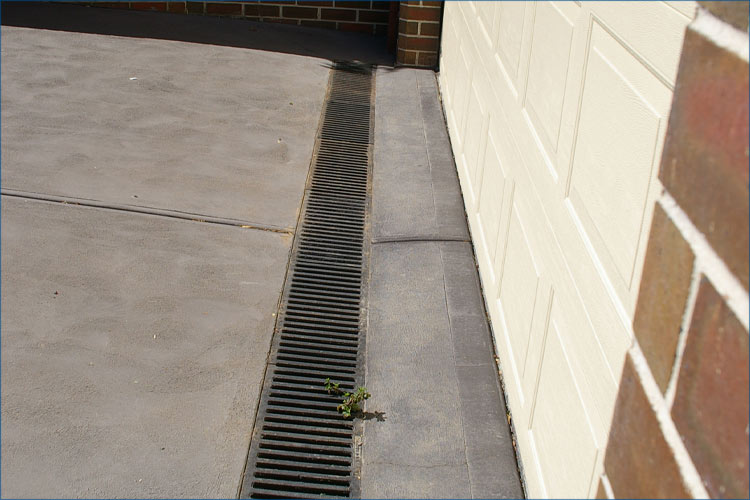 Residential photo of driveway leading to garage with specialised drainage solution.